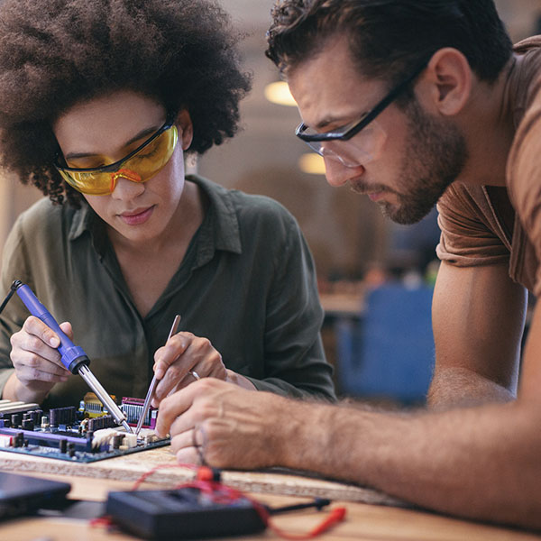 Co-workers working late on a circuit boards in office